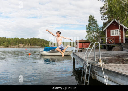 Boy jumping dal jetty Foto Stock