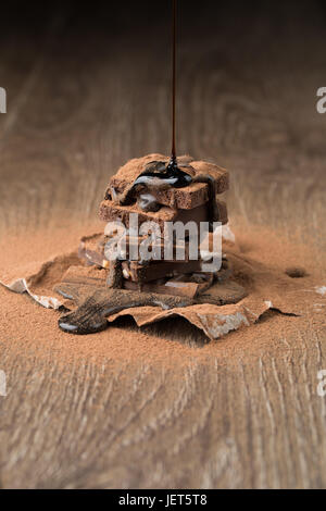 Piramide di cioccolato con sciroppo sul tavolo di legno con polvere di cacao su sfondo nero Foto Stock