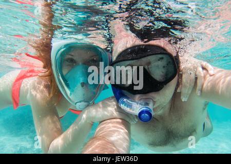 Una coppia in amore selfie tenendo sott'acqua in Oceano Indiano, Maldive. Turchesi acque cristalline. Foto Stock