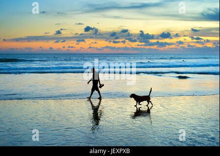 Silhouette di uomo e cane a camminare su una spiaggia al tramonto. Isola di Bali, Indonesia Foto Stock