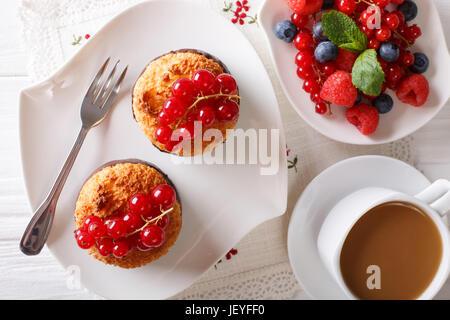 La deliziosa prima colazione, noce di cocco muffin, frutti di bosco e caffè con latte vicino sul tavolo. vista orizzontale dal di sopra