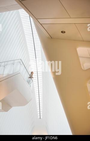 Una persona in piedi su un galleggiante balcone sospeso nello spazio aperto della atrium l'occhio al World Trade Foto Stock
