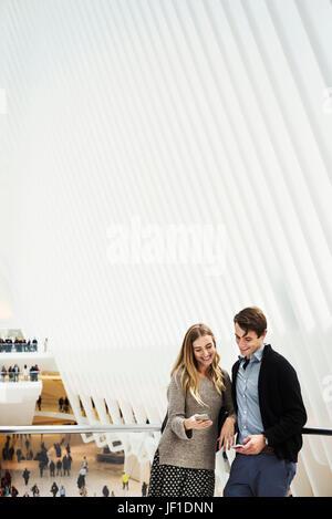 Due persone in piedi su un balcone condividendo una schermata telefono, con una panoramica dell'atrio centrale del Foto Stock
