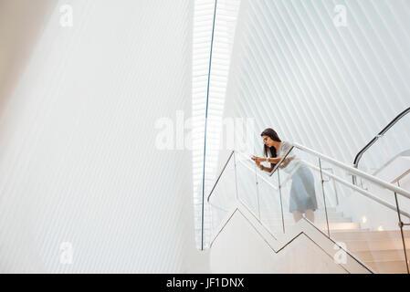 Una donna su per le scale appoggiate su di una ringhiera nel vasto spazio dell'atrio dell'occhio edificio al sito Foto Stock