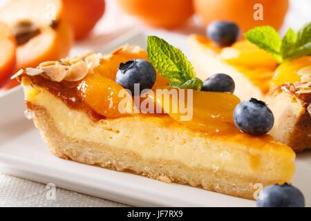 Un bel dessert: una cheesecake con albicocche, mirtilli e mandorle close-up su una piastra orizzontale. Foto Stock