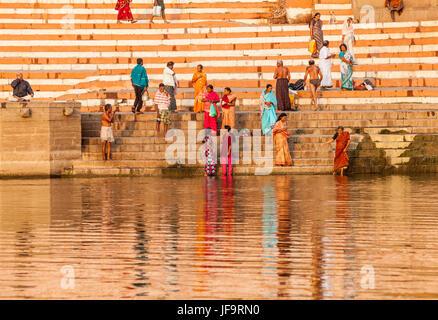Gli uomini e le donne a ghat di Varanasi, India sulle rive del fiume Gange. Uttar Pradesh. Foto Stock