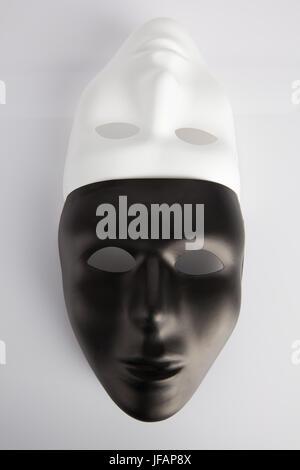 Bianco e nero maschere unita su bianco sfondo riflettente. L'immagine verticale, vista dall'alto. Concetto di anonimato.