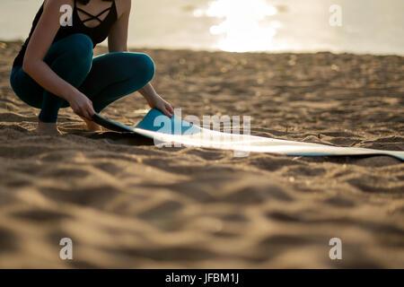 Attraente giovane donna verde di piegatura di yoga o tappetino fitness dopo aver lavorato presso la spiaggia.