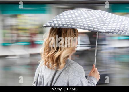 Sfocata persone con ombrelloni sulla strada di città in una piovosa giornata di primavera Foto Stock