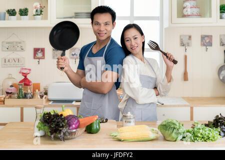 Giovani asiatici giovane preparare il cibo insieme al contatore in cucina. Felice amore giovane concetto. Foto Stock