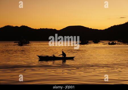 Tranquillo tramonto dietro le colline. Pescatore solitario pagaie una piccola barca che espone la sua rete da pesca. Foto Stock