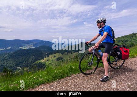 Uomo seduto sulla bicicletta guardando le montagne Foto Stock