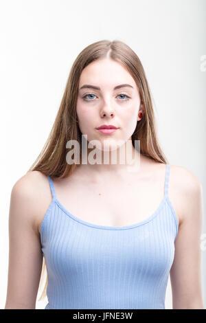 Grave athletic giovane donna in estate il top in piedi guardando intensamente la telecamera isolato su bianco Foto Stock