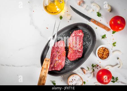 Carni, carni bovine. Crudo fresco bistecche in una padella. Le spezie (sale, pepe), verdure fresche - Pomodori, Foto Stock