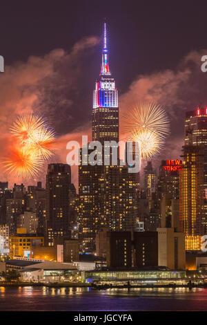 L annuale Macy's quarta di luglio mostra fuochi d'artificio illumina il cielo dietro la skyline di Manhattan a New York City come viste attraverso il fiume Hudson. Foto Stock