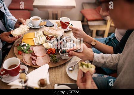 Close up di giovani seduti attorno al tavolo del bar e mangiare con focus su mani e cibo. Gruppo di studenti aventi Foto Stock