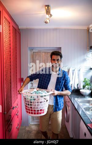 Ritratto di uomo con cesto per la biancheria mentre in piedi da lavello a home Foto Stock