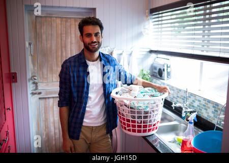 Ritratto di giovane uomo con cesto per la biancheria mentre in piedi da lavello a home Foto Stock