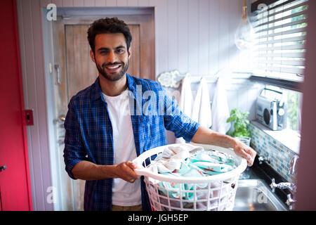 Ritratto di giovane sorridente uomo con cesto per la biancheria mentre in piedi dalla finestra a casa Foto Stock
