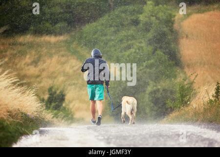 Giovane uomo che corre con il suo cane (labrador retriever) in heavy rain per la strada rurale. Foto Stock