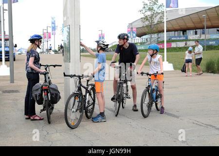 Famiglia con bici guardando al di fuori della mappa la Queen Elizabeth Olympic Park edificio velodromo di Stratford, Foto Stock