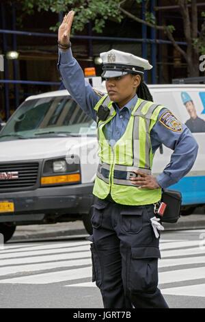 Un attraente poliziotta dirigere traffico su 34th Street a Manhattan, New York City Foto Stock