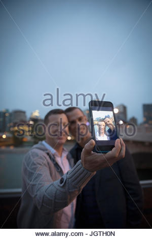 Maschio di coppia gay tenendo selfie con la fotocamera del telefono al fiume urbano waterfront Foto Stock