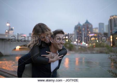 Giocoso coppia giovane piggybacking al fiume urbano waterfront al crepuscolo Foto Stock