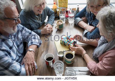 Senior amici festeggia il compleanno, apertura regalo in diner Foto Stock