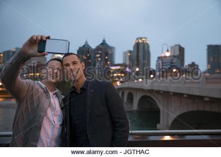 Maschio di coppia gay tenendo selfie con la fotocamera del telefono lungo waterfront urbano di notte Foto Stock