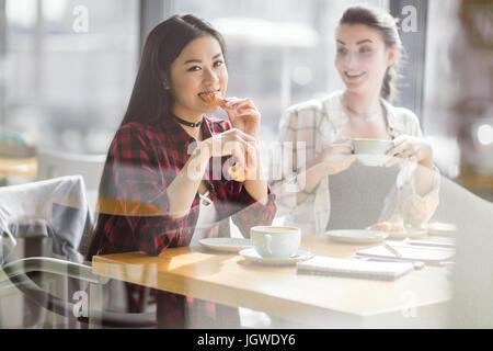 Le ragazze di mangiare croissant e caffè presso il cafe, coffee break Foto Stock