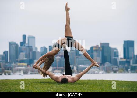 Giovane donna sdraiata sulla schiena in equilibrio su mani dell'uomo, la pratica dello yoga nella parte anteriore della skyline di Seattle Foto Stock