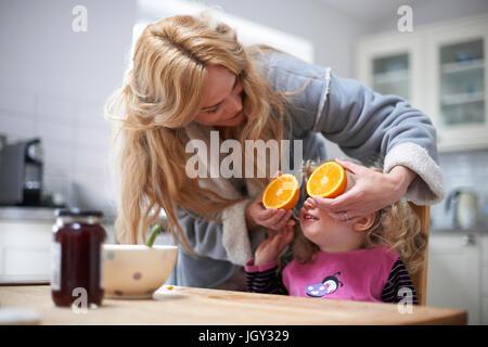 Giovane ragazza seduta al tavolo della cucina, madre holding dimezzato in arancione nella parte anteriore della Foto Stock