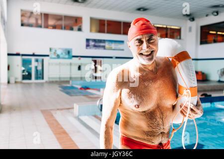 Senior uomo sul dazio bagnino holding galleggiante Foto Stock