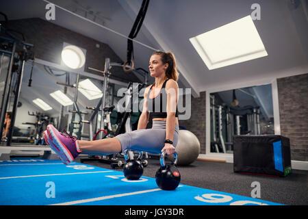 Giovane donna formazione, facendo sedere di push ups su bollitore campane in palestra Foto Stock