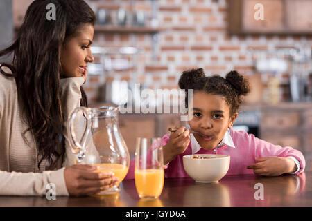 Ritratto di Madre e figlia di fare colazione insieme a casa Foto Stock