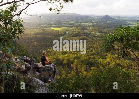 Un giovane uomo si siede tranquillamente, meditando sulla cima di una montagna con ampie vedute vicino a Noosa teste, Foto Stock