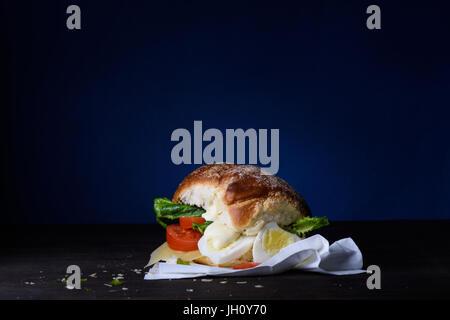 Deliziosi burger con uova, pomodoro, formaggio, lattuga contatore di legno. Copia dello spazio. Foto Stock