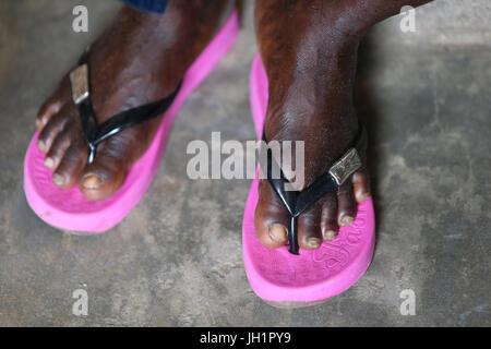 Donna con rosa flip-flop. Lomé. Il Togo. Foto Stock