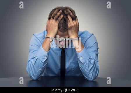 White Collar Crime concetto - disperato imprenditore con manette Foto Stock