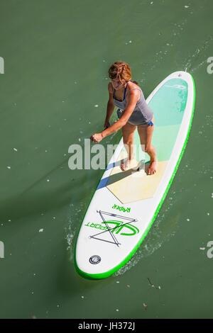 Donna stand up paddle imbarco su un fiume presa da sopra Foto Stock