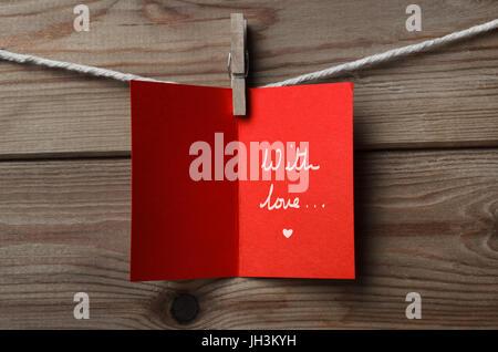 In rosso di un biglietto di auguri, ancorato alla stringa contro asse di legno aperto in background per visualizzare Foto Stock