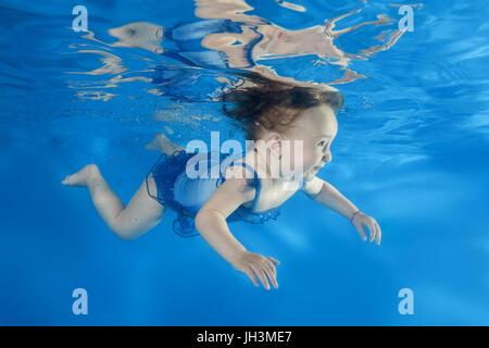 Bambina ha paura di nuotare sotto l'acqua in piscina Foto Stock