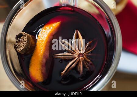 Tettuccio di close up (macro) colpo di un bicchiere di vin brulé con anice stellato, arancio e la stecca di cannella. Foto Stock