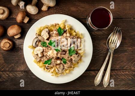 Carni bovine a fungo stroganoff con pasta all' uovo e vino rosso Foto Stock