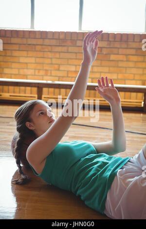 Femmina giocatore di basket gesticolando mentre vi rilassate sul pavimento in tribunale Foto Stock