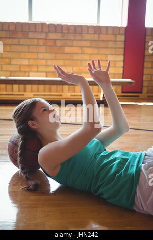 Donna gesticolando mentre vi rilassate sul pavimento nel campo di pallacanestro Foto Stock