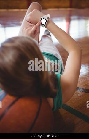 Femmina giocatore di basket utilizzando smart guardare mentre vi rilassate in tribunale Foto Stock