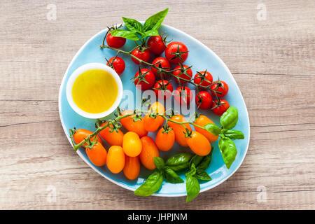 Varietà di pomodori ciliegia e le foglie di basilico su una piastra blu su un tavolo di legno. Ingredienti per l'estate Foto Stock