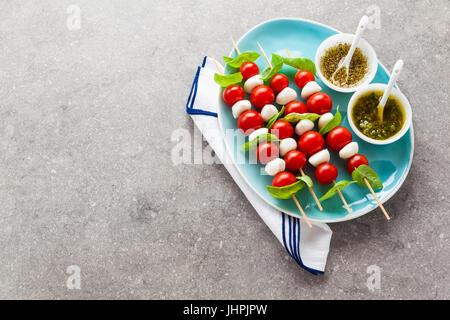 Appetitosi kebab vegetariani da pomodori ciliegia e mini mozzarella in due tipi di basilico e origano sugo come Foto Stock